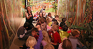 Lynn Koos, Curator, talks to students from Westfield Elementary School about items in a mural at the beginning of the Western Africa exhibit at the African American Museum of Iowa in Cedar Rapids on Friday, March 22, 2013.