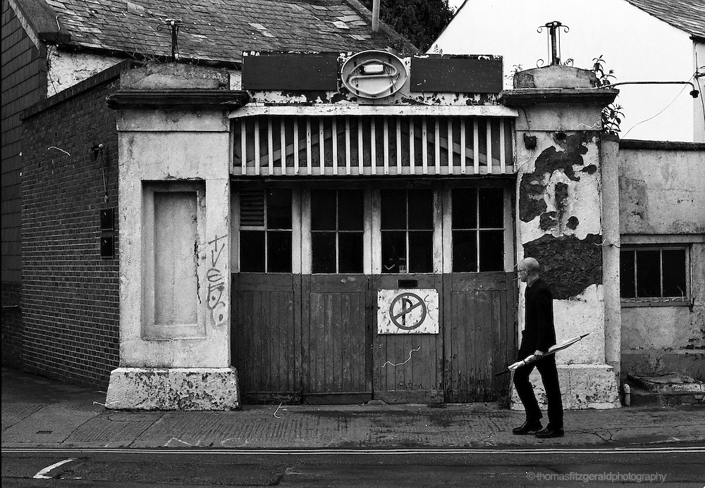 Dublin City, Ireland: A man walks by an old garage doorway which is warped and peeling from age. A black and white image shot on film. <br />