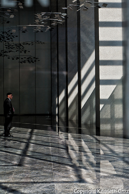 A security guard in a building on 8th Avenue and 42nd Street. He looks to be in an architectural prison.