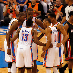 Jun 14, 2012; Oklahoma City, OK, USA;  Oklahoma City Thunder small forward Kevin Durant (left), and guard James Harden (13) and point guard Russell Westbrook (0) talk with teammates during the second quarter of game two in the 2012 NBA Finals against the Miami Heat at Chesapeake Energy Arena. Mandatory Credit: Derick E. Hingle-US PRESSWIRE