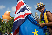 The inflatable balloon called Baby Trump flies above a Brexit protestor and the British Union Jack flag Parliament Square in Westminster, the seat of the UK Parliament, during the US President's visit to the UK, on 13th July 2018, in London, England. Baby Trump is a 20ft high orange blimp depicting the US President as an enraged, smartphone-clutching infant - and given special permission to appear above the capital by London Mayor Sadiq Khan because of its protest rather than artistic nature. It is the brainchild of Graphic designer Matt Bonner. (Photo by Richard Baker / In Pictures via Getty Images)