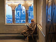 Eine aeltere Dame als Ordner liest im Turm des Altstaedter Rathaus - gegenueber der Teynkirche - waehrend ihrem Wachdienst ein Buch an einem verschneiten Tag in Prag.<br /> <br /> An older lady working as a guard at the Old Town City Hall on the opposite of Teyn church at Old Town Square reading a book during her shift in the city center of Prague.
