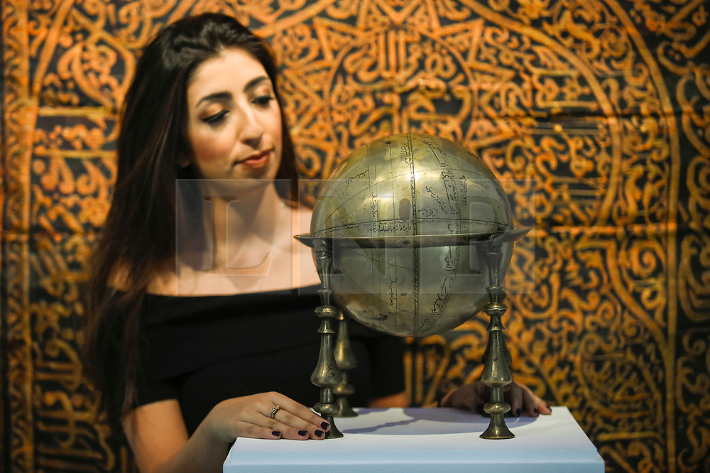 "© Licensed to London News Pictures. 18/10/2019. LONDON, UK. A staff member poses with a ""Safavid brass celestial globe and frame"", Persia, 17th century (Est. GBP80,000-120,000).  Preview of Islamic, Indian and Middle Eastern art to be auctioned at Sotheby's, New Bond Street, on 22 and 23 October.  Photo credit: Stephen Chung/LNP"