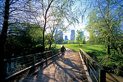 Stock photo of a girl riding her bicycle across a wooden bridge in Buffalo Bayou Park