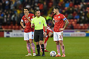 Kenny Dougall of Barnsley FC and Barnsley FC Captain Alex Mowatt speak with referee Kieth Stroud during the EFL Sky Bet Championship match between Barnsley and Queens Park Rangers at Oakwell, Barnsley, England on 14 December 2019.