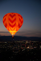 """Dawn Patrol 16"" - Photograph of a glowing hot air balloon flying for the Dawn Patrol at the 2012 Great Reno Balloon Race. Photographed from a hot air balloon."