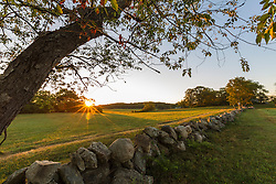 A stone wall and field at sunrise at the Cox Reservation in Essex, Massachusetts.