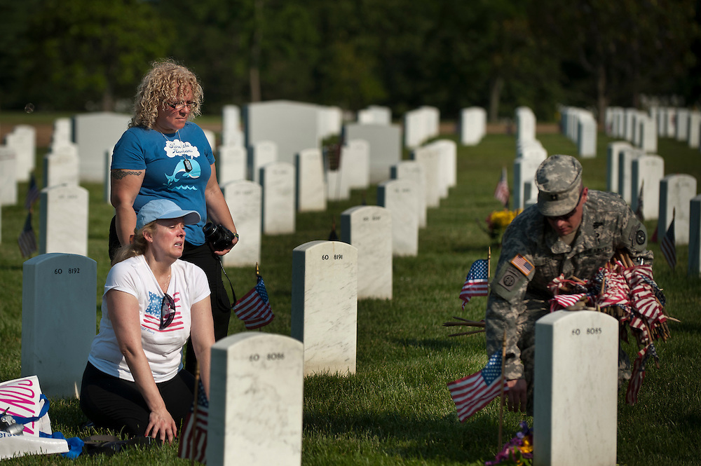 "DIANE FOX (kneeling) and EMILY TORO, both of New York City, look on as a member of the 3rd U.S. Infantry, known as The Old Guard, places an American flag in front of their friend's headstone in advance of the Memorial Day weekend. The tradition, known as ""flags in,"" is conducted annually since 1948. Every available soldier in the 3rd U.S. Infantry participates, placing small American flags one foot in front and centered before more than 260,000 gravestones and about 7,300 niches at the cemetery's columbarium. Old Guard soldiers remain in the cemetery throughout the weekend, ensuring that a flag remains at each gravestone."