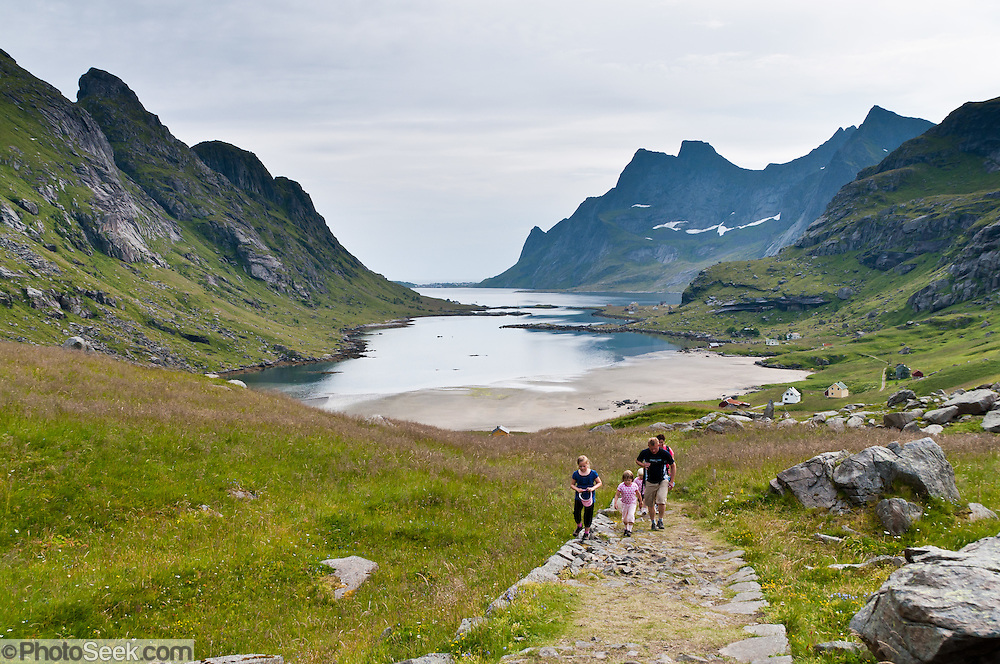 A family hikes from Bunesfjord (an arm of Reinefjord) on the easy mountain trail to Bunes Beach, on Moskenesøya (the Moskenes Island), part of Lofoten, an archipelago and traditional district in Nordland county, Norway.