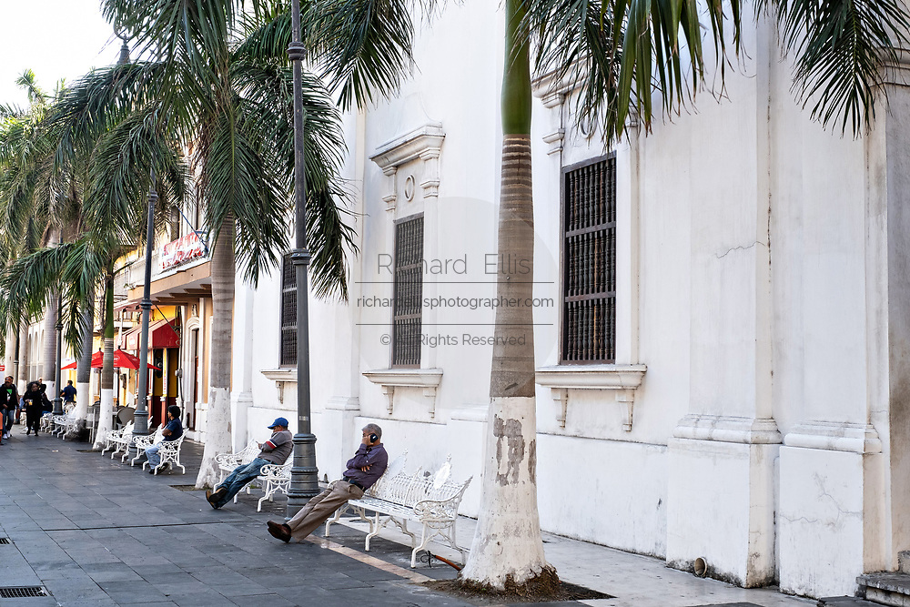 People rest on park benches along the Plaza de las Armas and the Portales de Veracruz in the historic center of the city of Veracruz, Mexico. The area is the main public square in Veracruz.