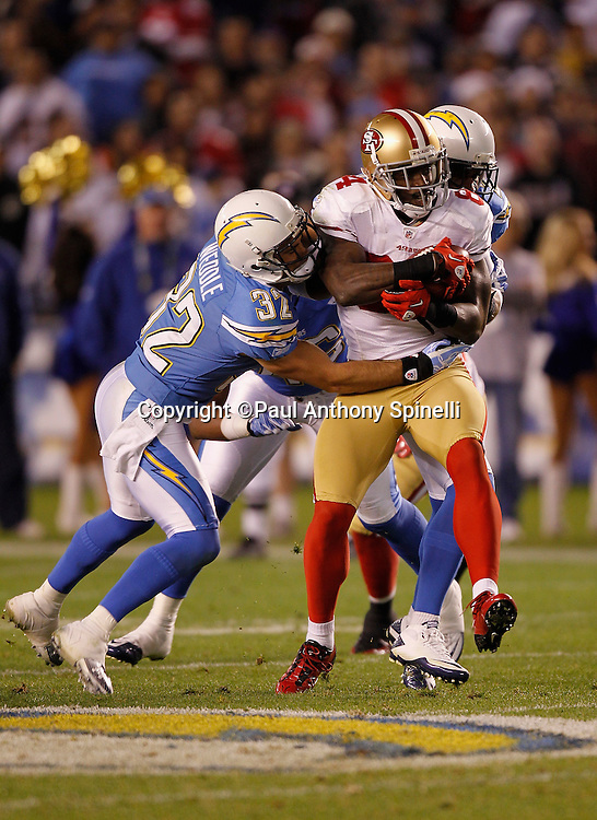 San Francisco 49ers wide receiver Josh Morgan (84) catches a 19 yard first down pass and gets tackled by San Diego Chargers safety Eric Weddle (32) and San Diego Chargers cornerback Quentin Jammer (23) during the NFL week 15 football game against the San Diego Chargers on Thursday, December 16, 2010 in San Diego, California. The Chargers won the game 34-7. (©Paul Anthony Spinelli)