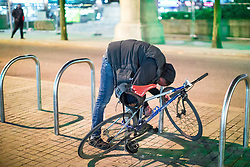 © Licensed to London News Pictures . 07/04/2017 . Manchester , UK . A man stands prone bent over a bike rack , unmoving , in what is believed to be the consequence of smoking spice , in Piccadilly Gardens . Greater Manchester Police have authorised dispersal powers and say they will ban people from the city centre for 48 hours , this evening (7th April 2017) , in order to tackle alcohol and spice abuse . Photo credit : Joel Goodman/LNP