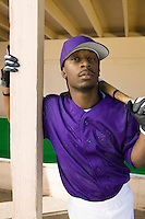 Baseball Player Standing in Dugout Holding Bat