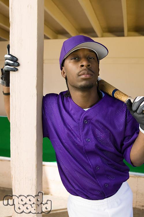 Baseball Player Standing in Dugout Holding Bat