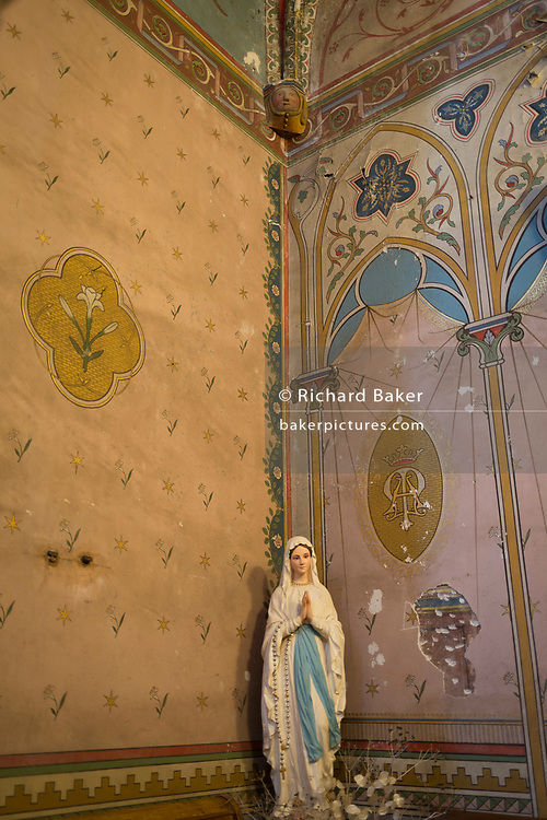 A figurine of Mary and wall decoration in the church of Sant-Michel, on 21st May 2017, in Lagrasse, Languedoc-Rousillon, south of France. Lagrasse is listed as one of France's most beautiful villages and lies on the famous Route 20 wine route in the Basses-Corbieres region dating to the 13th century.