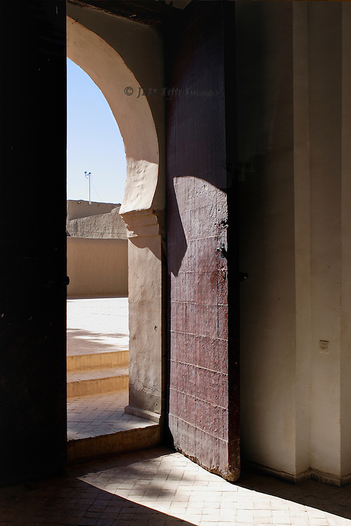Casbah doorway, from inside through Islamic archway toward the courtyard outside.  Passageway is emphasized by deep shadows and bright sunlight in contrast.  The heavy door stands open. A TV / radio aerial is visible above the mud brick wall of the adjoining courtyard.  It represents a liminal space in which one has come from the inside and is about to enter the outside.