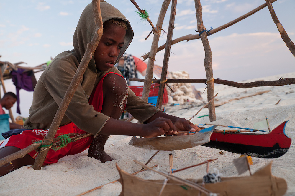 A Vezo boy living in a migrant fishing camp puts the finishing touches on a miniature sailing canoe.  It is much more than a toy: a replica of the real thing, he'll practise sailing with it and gain skill in repairing real pirogues.  Migrant children do not have the opportunity to go to school, but spend hours occupying themselves with games that will one day make them skilled fishers.