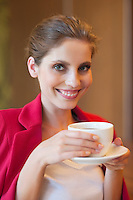 Portrait of a beautiful young woman holding coffee cup