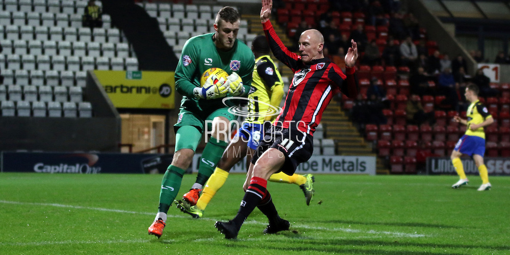 Kevin Ellison challenges during the Sky Bet League 2 match between Morecambe and Dagenham and Redbridge at the Globe Arena, Morecambe, England on 1 December 2015. Photo by Pete Burns.