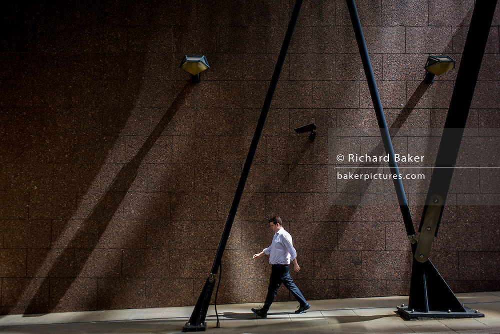 Strangers walk beneath urban landscape of modern architecture at Broadgate in the City of London.