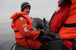 USA ALASKA CHUKCHI SEA 29JUL12 - Videographer Adams Wood of the USA and Greenpeace boat crew survey the sea ice in the Chukchi Sea near a proposed Shell drill site north of Point Hope, Alaska...Photo by Jiri Rezac / Greenpeace....© Jiri Rezac / Greenpeace