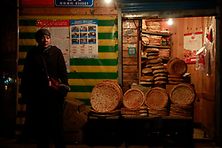 An ethnic Uighur woman stands beside a shop selling nan bread in Urumqi city, Xinjiang Uighur Autonomous Province, China, 18 November 2017. Uighurs, a Muslim ethnic minority group in China, make up about 40 per cent of the 21.8 million people in Xinjiang, a vast, ethnically divided region that borders Pakistan, Afghanistan, Kazakhstan, Kyrgyzstan and Mongolia. Other ethnic minorities living in here include the Han Chinese, Kyrgyz, Mongolian and Tajiks people. Xinjiang has long been subjected to separatists unrests and violent terrorist attacks blamed by authorities on Islamist extremism while human rights groups say Chinese repression on religious rights, culture and freedom of movement caused undue tensions. Life however goes on under the watchful eye of the government for the ethnic Uighurs living in the city of Urumqi and surrounding areas and the region is still considered an attractive tourist spot. A recent report by state media Xinhua news agency claims Xinjiang received more than 100 million tourists in 2017, 'the highest figure in its history'.