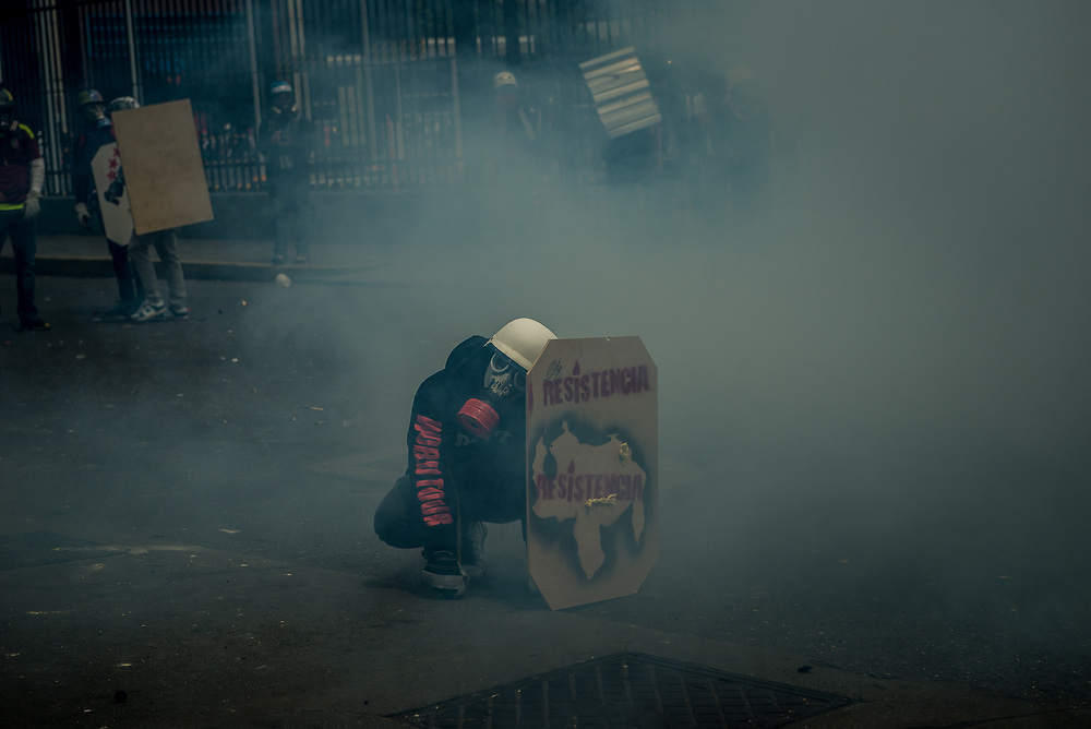 CARACAS, VENEZUELA - MAY 8, 2017:  Anti-government protesters use homemade shields and throw rocks and molotov cocktails at members of the National Police, who responded by heavily tear gassing and firing rubber bullets and buckshot at them.  The streets of Caracas and other cities across Venezuela have been filled with tens of thousands of demonstrators for nearly 100 days of massive protests, held since April 1st. Protesters are enraged at the government for becoming an increasingly repressive, authoritarian regime that has delayed elections, used armed government loyalist to threaten dissidents, called for the Constitution to be re-written to favor them, jailed and tortured protesters and members of the political opposition, and whose corruption and failed economic policy has caused the current economic crisis that has led to widespread food and medicine shortages across the country.  Independent local media report nearly 100 people have been killed during protests and protest-related riots and looting.  The government currently only officially reports 75 deaths.  Over 2,000 people have been injured, and over 3,000 protesters have been detained by authorities.  PHOTO: Meridith Kohut