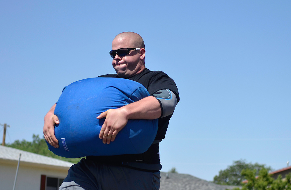 JD070811b/Sports/07.09.11/Jessica Dyer.John Posen trains for his strongman competitions by carrying large sandbags up the street in front of his Northeast Heights home..Albuquerque, New Mexico(Albuquerque Journal)