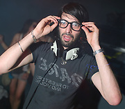 Erol Alkan wearing glasses and headphone round his neck, Masonic Place, Nottingham.