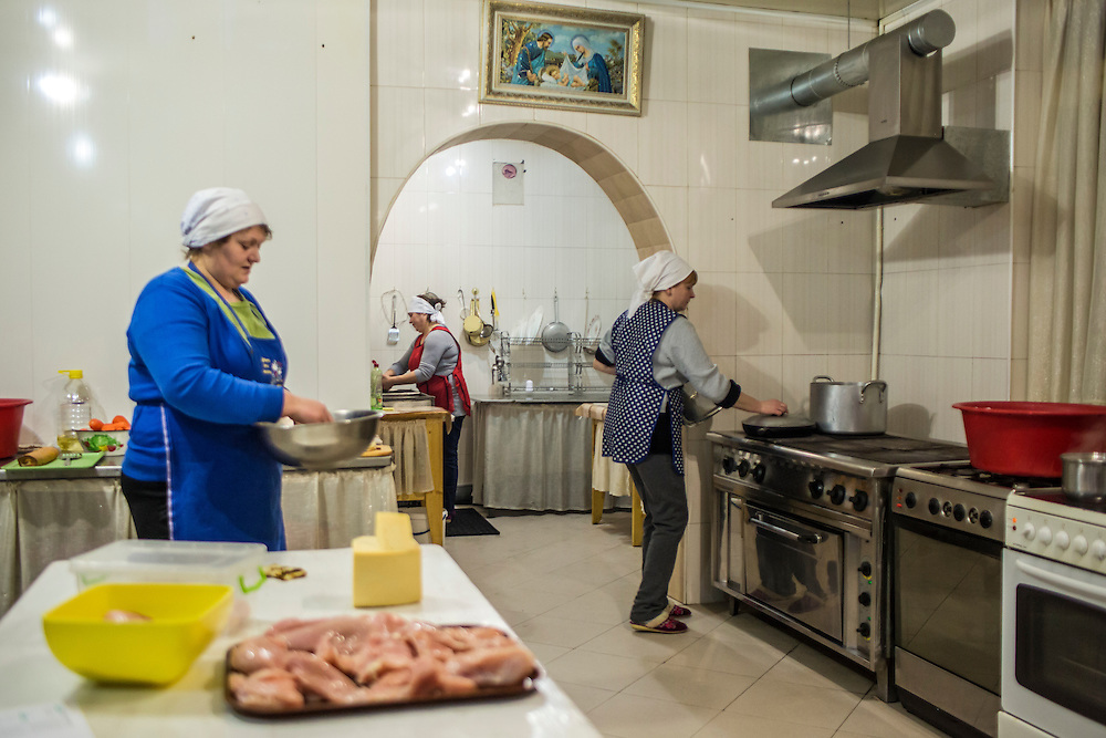 "Maria Erman, 34, Anna Istratii, 48, and Nadiya Federko, 43, from left, prepare food in the kitchen of the Mariana Restaurant for large crowds expected the following day when the Malanka Festival takes place on Wednesday, January 13, 2016 in Krasnoilsk, Ukraine. ""We are preparing for the end of the world tomorrow,"" Federko joked."