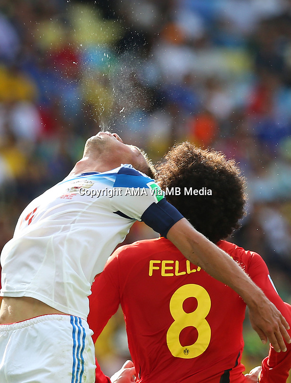 Vasiliy Berezutskiy of Russia spits out after winning a header with Marouane Fellaini of Belgium