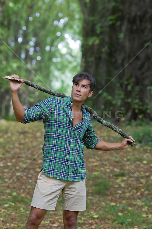 Asian American man holding a branch on his shoulders out in the woods