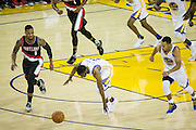 Golden State Warriors guard Ian Clark (21) stumbles as guard Stephen Curry (30) and Portland Trail Blazers guard Damian Lillard (0) chase down the loose ball at Oracle Arena in Oakland, Calif., on October 21, 2016. (Stan Olszewski/Special to S.F. Examiner)