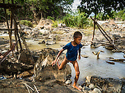 17 JUNE 2016 - DON KHONE, CHAMPASAK, LAOS:  A boy runs past fish traps along the riverbank near Khon Pa Soi Waterfalls, on the east side of Don Khon. It's the smaller of the two waterfalls in Don Khon. Fishermen have constructed an elaborate system of rope bridges over the falls they use to get to the fish traps they set. Fishermen in the area are contending with lower yields and smaller fish, threatening their way of life. The Mekong River is one of the most biodiverse and productive rivers on Earth. It is a global hotspot for freshwater fishes: over 1,000 species have been recorded there, second only to the Amazon. The Mekong River is also the most productive inland fishery in the world. The total harvest of fish from the Mekong is approximately 2.5 million metric tons per year. By some estimates the harvest in the Tonle Sap (in Cambodia) had doubled from 1940 to 1995, but the number of people fishing the in the lake has quadrupled, so the harvest per person is cut in half. There is evidence of over fishing in the Mekong - populations of large fish have shrunk and fishermen are bringing in smaller and smaller fish.        PHOTO BY JACK KURTZ