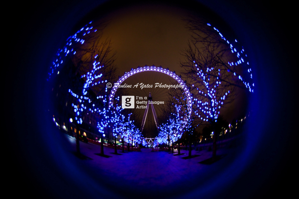 The iconic London Eye, lit up blue in winter. Taken from Jubilee Walk.