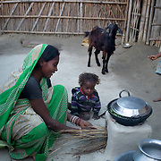India. Bihar. Motihari. A mother prepares supper on her eco stove.