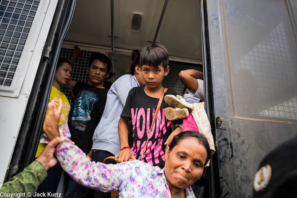 16 JUNE 2014 - POIPET, CAMBODIA: Cambodian migrants returning from Thailand get out of a Thai immigration police truck in Poipet, Cambodia. More than 150,000 Cambodian migrant workers and their families have left Thailand since June 12. The exodus started when rumors circulated in the Cambodian migrant community that the Thai junta was going to crack down on undocumented workers. About 40,000 Cambodians were expected to return to Cambodia today. The mass exodus has stressed resources on both sides of the Thai/Cambodian border. The Cambodian town of Poipet has been over run with returning migrants. On the Thai side, in Aranyaprathet, the bus and train station has been flooded with Cambodians taking all of their possessions back to Cambodia.  PHOTO BY JACK KURTZ