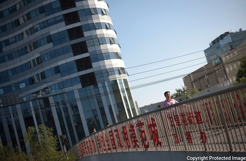 A Chinese man walks on an overpass near the new SOHO complex in Beijing. Construction of new commercial and residential complexes continue to sprout up in Beijing in spite an economy that is showing signs of cooling.