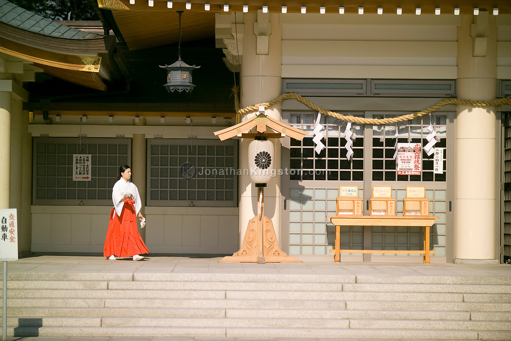 A Ujiko walks in front of the entrance to the Hiroshima Gokoku Shrine in Hiroshima, Japan.  The Gokoku shrine is a Shinto shrine located within the innermost moat of Hiroshima castle.  A Ujiko is a person from the local populace who help maintain the shrine.