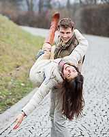 Portrait of happy man carrying woman in park