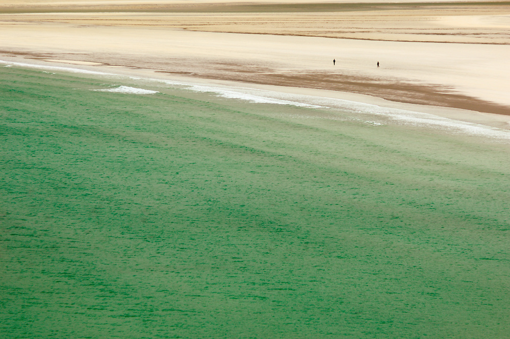 Two figures walking on Luskentyre Beach at low tide