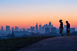 London, December 12 2017. A jogger and a walker are in silhouette against the skyline before the sun rises on a clear very cold morning in London, seen from Primrose Hill in Camden. © Paul Davey