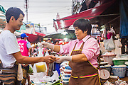 "03 OCTOBER 2012 - BANGKOK, THAILAND:     A vendor concludes a sale in Khlong Toey Market in Bangkok. Khlong Toey (also called Khlong Toei) Market is one of the largest ""wet markets"" in Thailand. Thousands of people shop in the sprawling market for fresh fruits and vegetables as well meat, fish and poultry every day.        PHOTO BY JACK KURTZ"