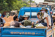 09 MARCH 2013 - ALONG HIGHWAY 13, LAOS:  RIders in the back of a truck on Highway 13 in rural Vientiane province, Laos. The paving of Highway 13 from Vientiane to near the Chinese border has changed the way of life in rural Laos. Villagers near Luang Prabang used to have to take unreliable boats that took three hours round trip to get from the homes to the tourist center of Luang Prabang, now they take a 40 minute round trip bus ride. North of Luang Prabang, paving the highway has been an opportunity for China to use Laos as a transshipping point. Chinese merchandise now goes through Laos to Thailand where it's put on Thai trains and taken to the deep water port east of Bangkok. The Chinese have also expanded their economic empire into Laos. Chinese hotels and businesses are common in northern Laos and in some cities, like Oudomxay, are now up to 40% percent. As the roads are paved, more people move away from their traditional homes in the mountains of Laos and crowd the side of the road living off tourists' and truck drivers.    PHOTO BY JACK KURTZ