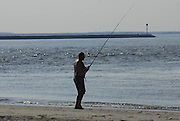 Fisherman fishing on beach at Cape Henlopen State Park, Delaware