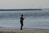 Fisherman fishing on beach at Cape Henlopen State Park, Delaware