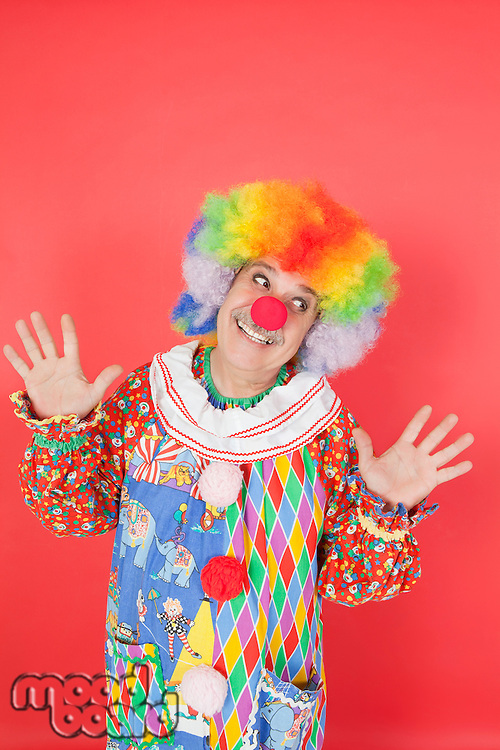 Funny clown with arms raised looking away against colored background