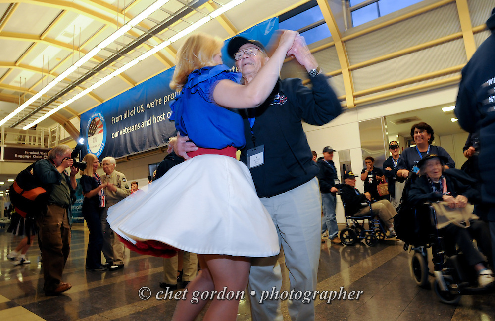 WWII Veteran William Rudy (right) dances with swing dancer Theresa Werner at Reagan National Airport in Arlington, VA on Saturday, October 18, 2014. Seventy-five WWII Veterans from the Westchester County area toured the WWII Memorial and Arlington National Cemetery onboard the inaugural flight from Westchester County Airport in White Plains, NY. Hudson Valley Honor Flight is a chapter of the Honor Flight Network, which provides free flights for WWII Veterans and tours of the WWII Memorial constructed in their honor, and other sites in the nation's capital.  © Chet Gordon / Westchester Magazine