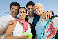 Four mixed doubles tennis players by net at tennis court portrait