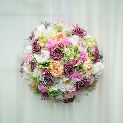 Suspended flower bouquet against an off-white linen background.
